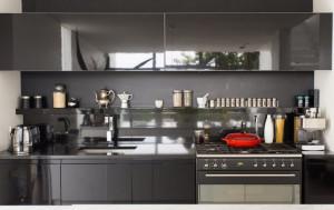 Vista de la cocina en color negro de casa angosta