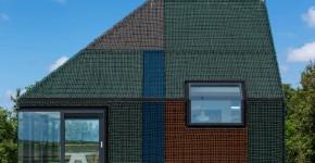 Casa pequeña de madera cubierta de redes de colores