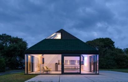 Vista frontal de la casa de campo con grandes ventanas