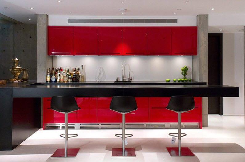 Muebles de color rojo y las encimeras e isla de cocina de color negro