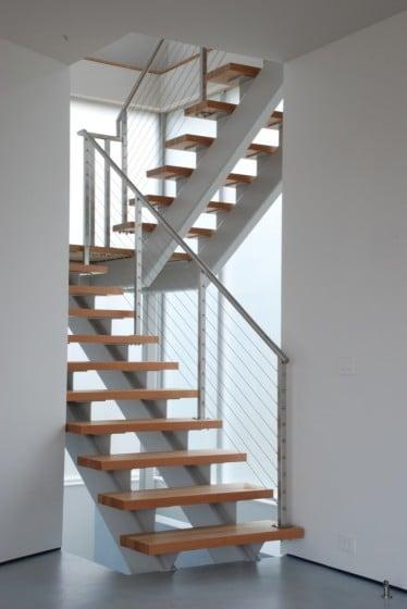 Diseño de modernas escaleras con peldaños de madera y barandas de hierro