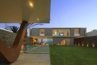 Fachada posterior de casa de dos pisos con piscina