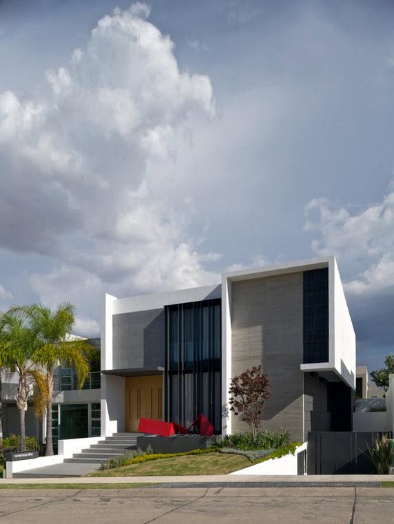 fachada de la casa de dos plantas con una pequea escultura de arte moderno en el ingreso principal