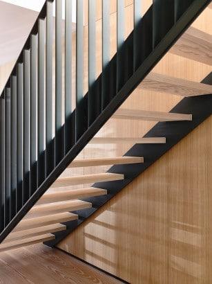 Detalles de escaleras modernas peldaños de madera y pasamano de hierro
