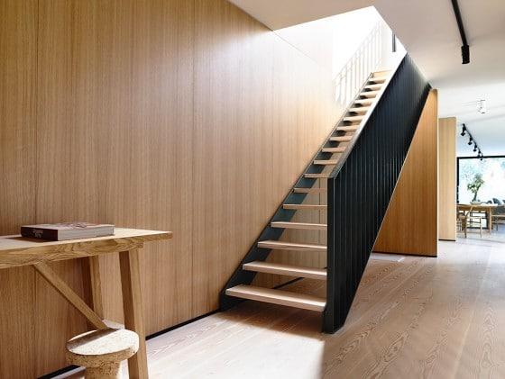 Diseño de escaleras modernas de peldañas de madera y pasamano de hierro