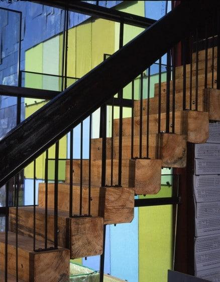 Diseño de escaleras con peldaños de troncos de madera y pasamanos de acero