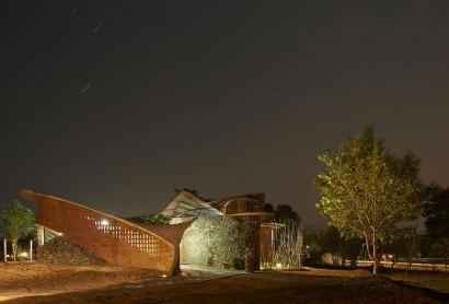 Fachada de casa rústica orgánica por la noche