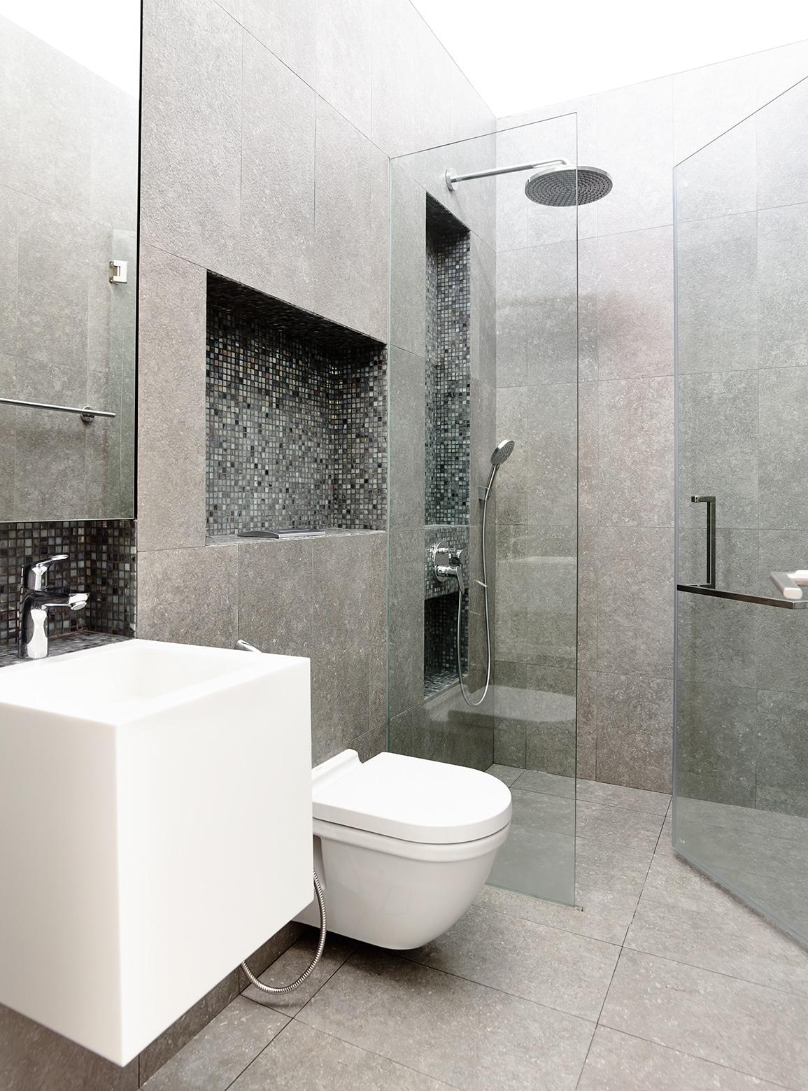 Baños Gris Con Blanco:Sanitarios blancos y cerámicos en tonos grises hacen contraste en el