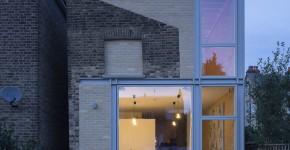 Fachada de casa moderna de dos pisos con acabados de ladrillo