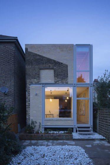 Fachada de casa rústica- moderna de dos pisos con acabados de ladrillo