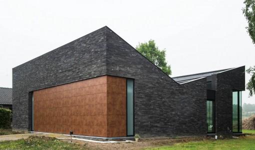 casa moderna de un piso y dos dormitorios tiene techos inclinados hacia dentro que la hacen destacar frente a vecinas