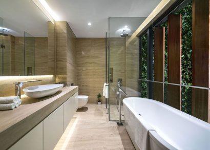 Diseño de cuarto de baño con marmol y sanitarios blancos