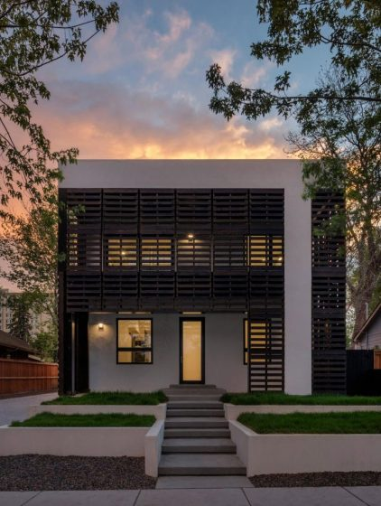 Fachada de casa de dos pisos con persianas de madera