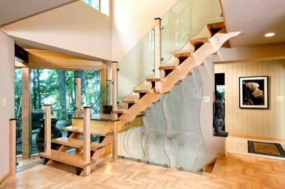 Diseño de escalera con madera ondulada y pasamanos cristal