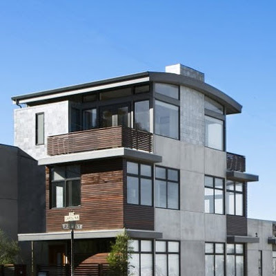 Fachada rústica de tres niveles con balcones