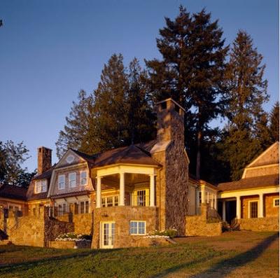 Fachada de casa rústica en el campo con chimenea