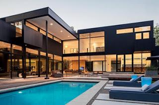 Fachada de casa en color negro con piscina al frente