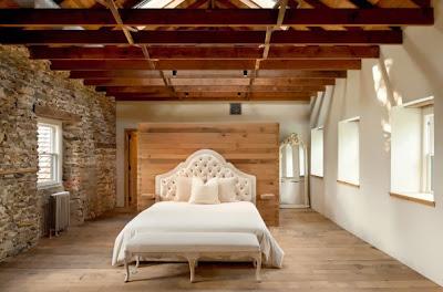 Diseño de dormitorio rústico con pared de piedra