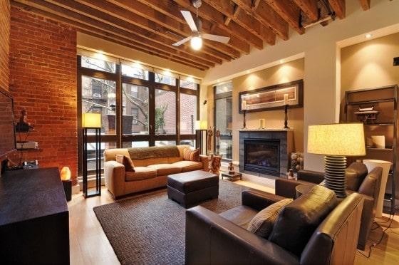 Diseño de apartamento con chimenea y elementos de madera y ladrillo