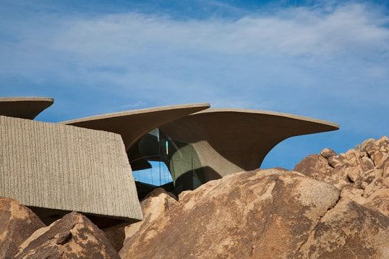 Fachada de casa orgánica mostrando las estructuras del techo