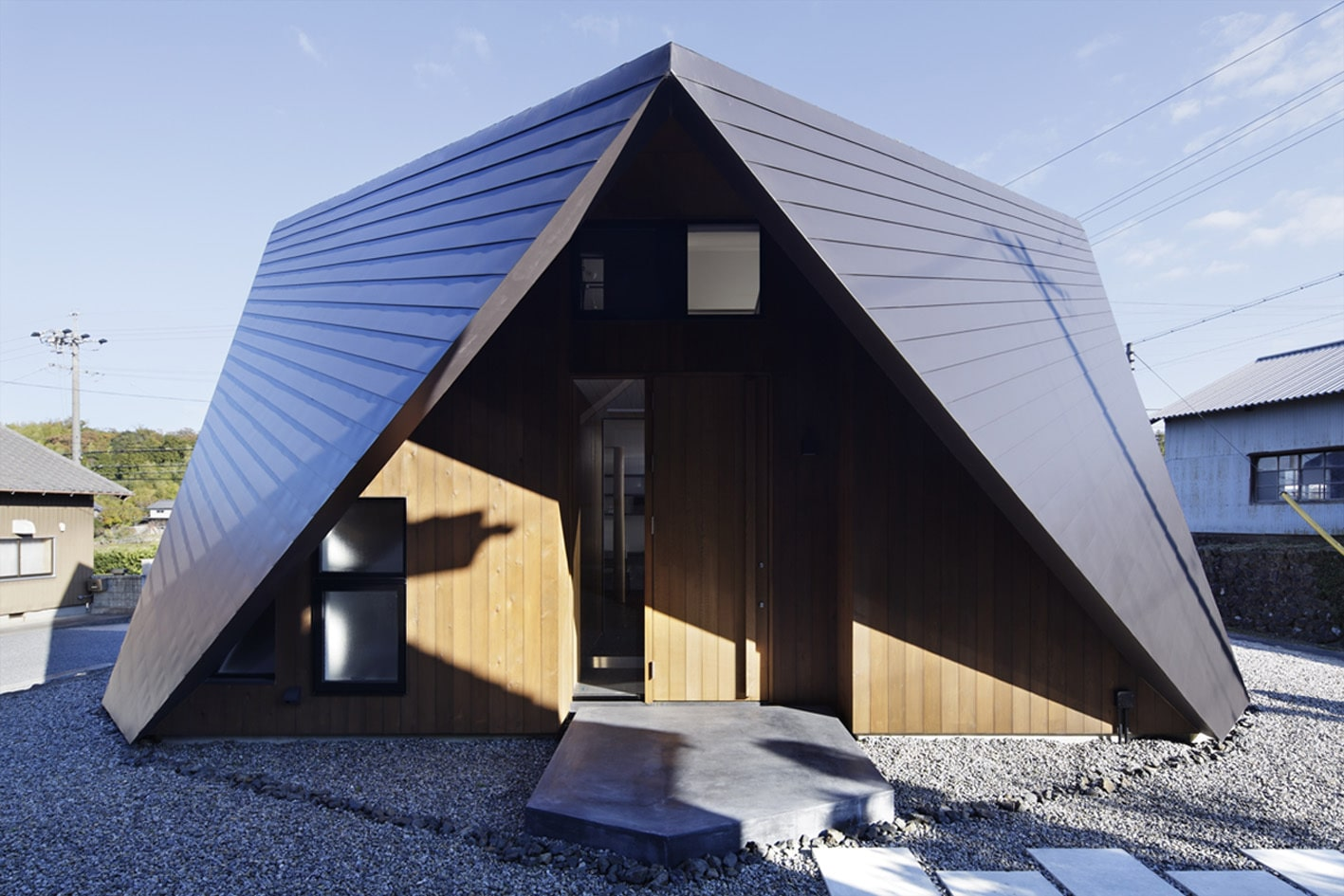 Casa de dos pisos con techo tipo origami para protecci n for Sobretechos para casas