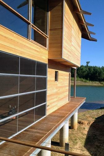Fachada lateral de casa de madera sobre el lago