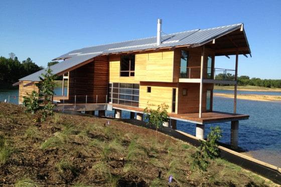 Fachada de casa de madera  a dos aguas sobre lago
