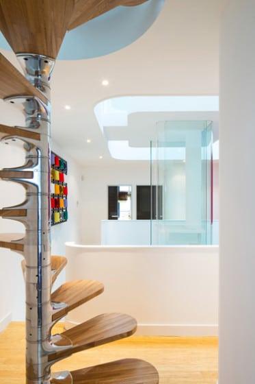 Diseño de escaleras caracol con centro plateado y pasos de madera