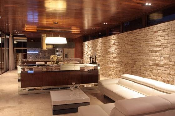 Diseño de interiores de la sala con  pared de piedra y muebles blancos