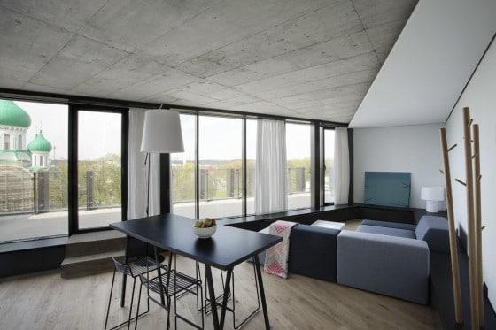 Diseño de sala triangular con falso techo y pisos de madera