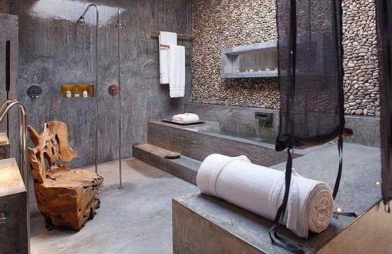 Diseño original de cuarto de baño con pared de piedra rodada y pared de cemento