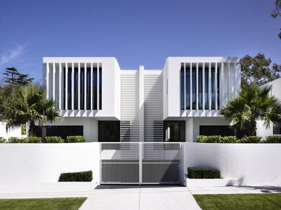 Fachada blanca de casa de dos pisos dividida en dos