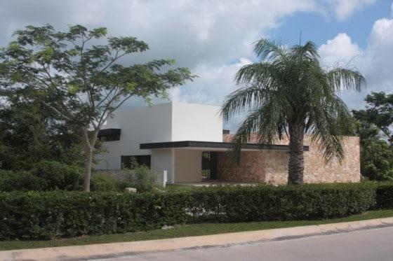 Fachada de casa en forma de L con pared de piedra