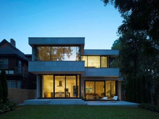 Fachada posterior de casa de dos plantas moderna iluminada por la noche