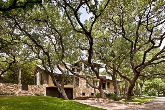 Hermosa casa rústica de piedra rodeado de grandes árboles