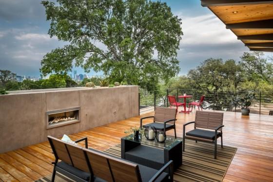Diseño de terraza con chimenea y piso de madera