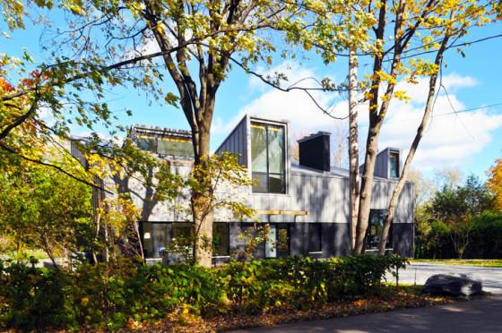 Fachada de casa autosustentable con grandes ventanas