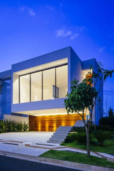 Fachada de casa moderna de dos pisos iluminada