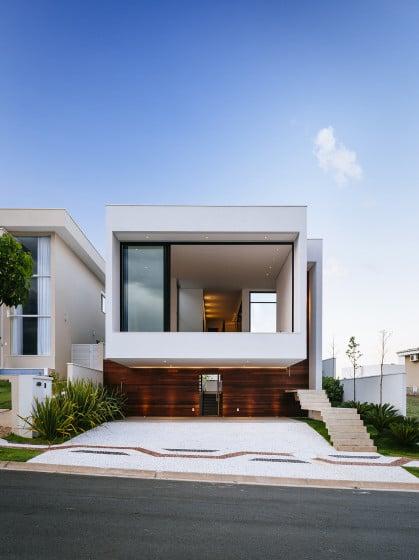 Fachada de casa moderna de dos pisos con volumen superior volado