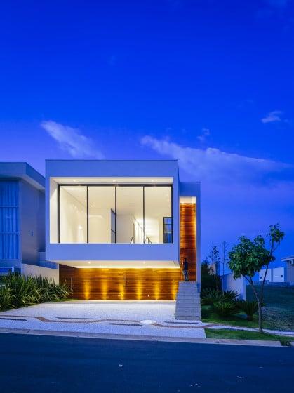 Fachada de moderna casa de dos pisos iluminada por la noche