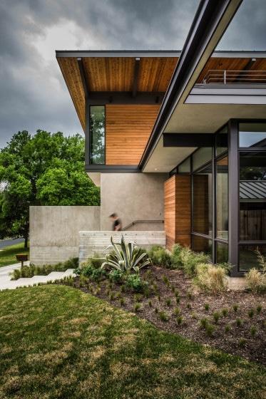 Fachada lateral de casa de dos pisos con enchape de madera y hormigón