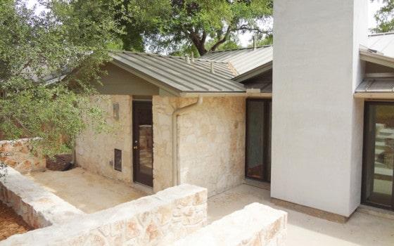 Fachada posterior de casa rural con acabados de piedra