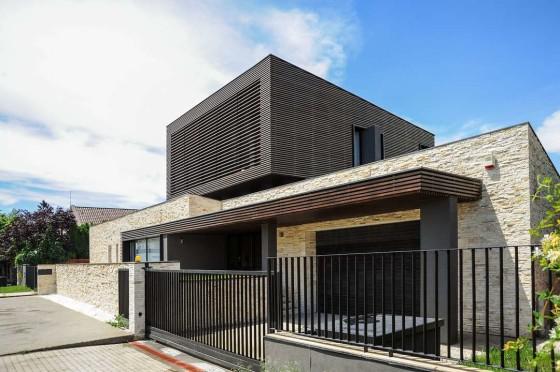 Fachada de casa moderna de piedra y madera de dos pisos