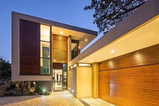 Fachada de moderna casa de dos pisos con estacionamiento