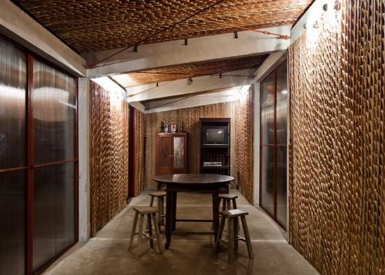 Diseño interior de casa con paredes de palmera y columnas de hormigón