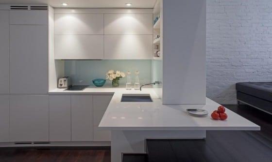 Diseño de cocina de mini departamento con muebles blancos