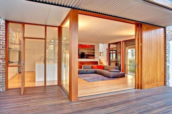 Diseño de sala y cocina con grandes ventanas y puertas