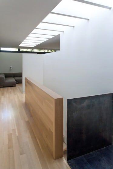 Diseño de pasadizo moderno con iluminación  natural por techo