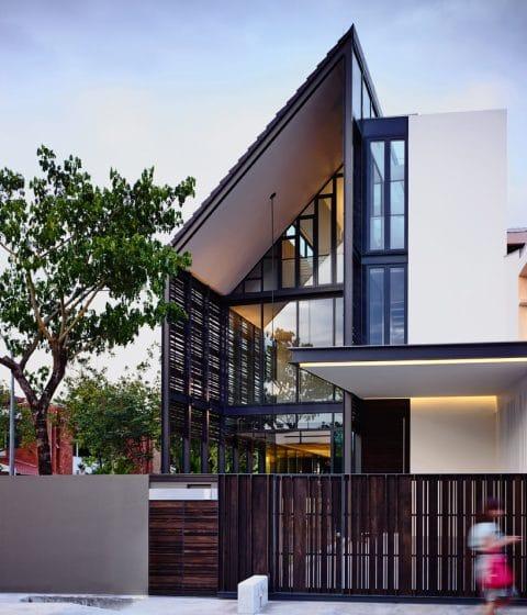 Fachada de moderna casa de dos pisos con atico