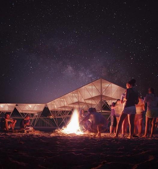 Casas de bambú para surfistas iluminadas por la noche